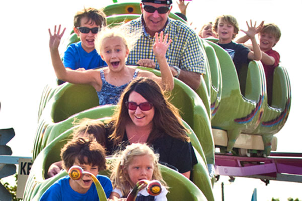 Kids with hands up while riding the wacky worm
